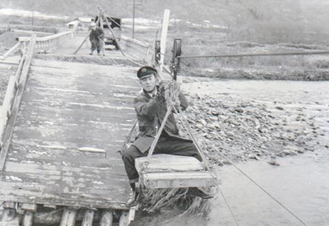 橋が決壊し、綱渡りで荷物を運ぶ社員