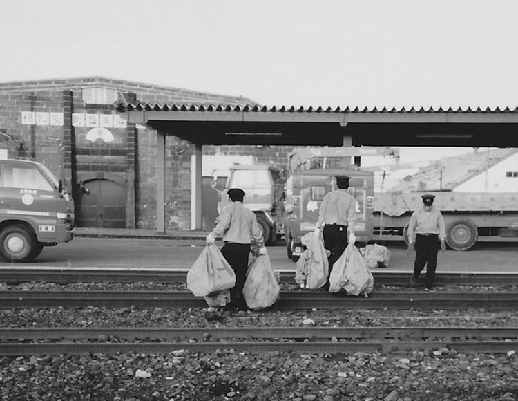 鉄道郵便に荷物を運ぶ社員が写った写真